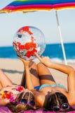 Madre joven e hija que miran la bola del globo del mundo foto de archivo