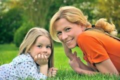Madre joven e hija que ponen en la hierba Imagen de archivo libre de regalías