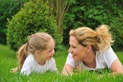 Madre joven e hija que ponen en la hierba Fotos de archivo