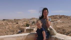 Madre joven e hija que presentan para la foto en fondo beduino del pueblo almacen de metraje de vídeo