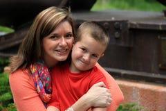 Madre joven e hijo que sonríen brillantemente mientras que abrazan Imagen de archivo