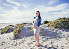 Madre joven embarazada a ser, colocándose al aire libre de mirada de la cámara, escena de la playa Fotografía de archivo libre de regalías