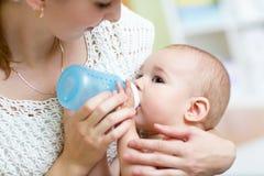 Madre joven en casa que alimenta al bebé con la botella de leche Foto de archivo libre de regalías