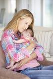 Madre joven en Sofa At Home Imagenes de archivo