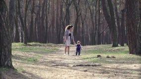 Madre joven en un paseo en naturaleza con su hijo del niño almacen de video
