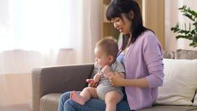 Madre joven feliz con el pequeño bebé en casa metrajes