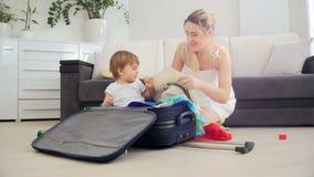 Madre joven feliz con su maleta del embalaje del hijo del niño para las vacaciones de verano almacen de metraje de vídeo