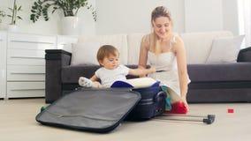 Madre joven feliz con su maleta del embalaje del hijo del niño para las vacaciones de verano almacen de video