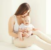 Madre joven feliz que besa al bebé lindo en casa Fotografía de archivo
