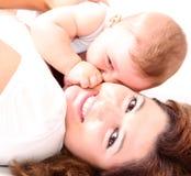 Madre joven feliz que besa a un bebé Imagen de archivo
