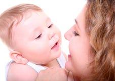 Madre joven feliz que besa a un bebé Fotografía de archivo