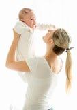 Madre joven feliz que celebra sus 3 meses del bebé en la ventana Imagenes de archivo