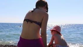Madre joven feliz que juega con su niño en la playa en un fondo del mar azul HD lleno 1920x1080 metrajes
