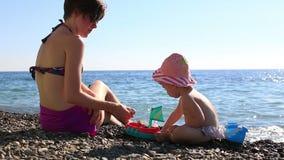 Madre joven feliz que juega con su niño en la playa en un fondo del mar azul HD lleno 1920x1080 almacen de metraje de vídeo