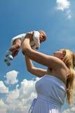 Madre joven feliz que levanta su colmo del bebé para arriba Imágenes de archivo libres de regalías