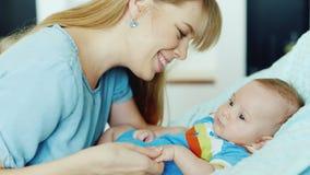 Madre joven feliz que mira a su niño, sosteniendo su pluma metrajes