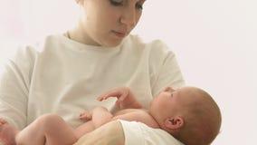 Madre joven feliz que oscila a su bebé recién nacido en sus brazos almacen de metraje de vídeo