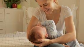 Madre joven feliz que oscila sus 3 meses del bebé en cama en el dormitorio almacen de video