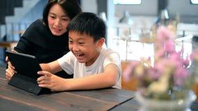 Madre joven feliz que usa la tableta con su hijo en el café almacen de video