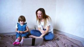 Madre joven feliz y pequeña hija que juegan junto en compu imagen de archivo