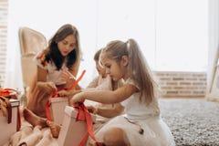 Madre joven feliz y sus dos hijas encantadoras en dresse agradable imagen de archivo libre de regalías
