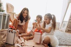 Madre joven feliz y sus dos hijas encantadoras en dresse agradable imagenes de archivo