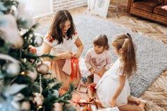 Madre joven feliz y sus dos hijas encantadoras en dresse agradable fotografía de archivo libre de regalías
