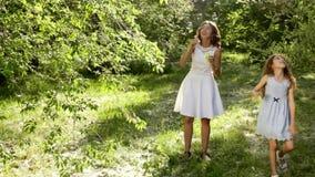 Madre joven hermosa así como su hija en la naturaleza que hace burbujas de jabón almacen de metraje de vídeo