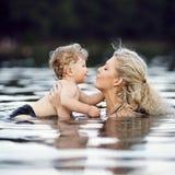 Madre joven hermosa con el hijo en agua Imágenes de archivo libres de regalías
