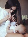 Madre joven hermosa con el pelo oscuro largo que presenta con su pequeño bebé adorable imagen de archivo
