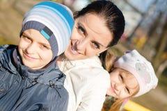 madre joven hermosa de 3 personas con dos niños, el hijo y la hija teniendo en cámara sonriente de la diversión y de mirada feliz Fotos de archivo