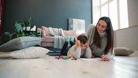Madre joven hermosa en un suéter caliente que miente en el piso con mi dibujo del hijo con los marcadores en el papel que retrata