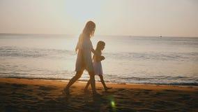 Madre joven hermosa feliz y pequeña hija que caminan juntas llevando a cabo las manos en el complejo playero tropical épico del m almacen de video