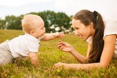 Madre joven hermosa que da la flor a su bebé Imagen de archivo
