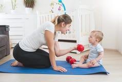 Madre joven hermosa que enseña a su hijo del bebé que hace aptitud en casa Fotos de archivo