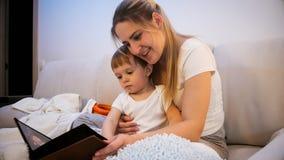 Madre joven hermosa que se sienta con su hijo del niño en cama y que lee cuento foto de archivo