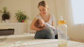 Madre joven hermosa que se sienta en cama y que oscila sus 3 meses del bebé después de alimentarlo almacen de video
