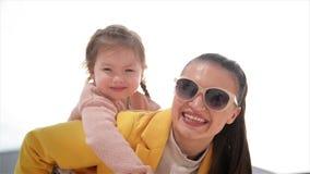 Madre joven hermosa y feliz que da a cuestas paseo a su hija E Ciudad del verano almacen de video