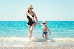 Madre joven hermosa y pequeño hijo que llevan a cabo las manos que corren en las ondas en la playa Fotografía de archivo libre de regalías