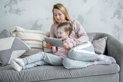 Madre joven hermosa y sus pequeñas películas del reloj de la hija junto, juego en la tableta y disfrutar sentarse en el sofá Abra imagen de archivo