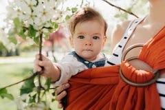Madre joven irreconocible con su bebé infantil en honda imagen de archivo