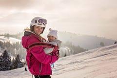 Madre joven, llevando a su bebé en la honda, subiendo en el pico w fotos de archivo