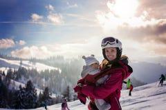 Madre joven, llevando a su bebé en la honda, subiendo en el pico w foto de archivo