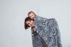 Madre joven moderna que lleva a su bebé en una honda imagenes de archivo