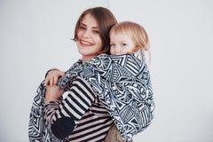 Madre joven moderna que lleva a su bebé en una honda fotos de archivo libres de regalías