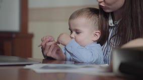 Madre joven ocupada que trabaja en casa con el beb? en sus revestimientos El dibujo del muchacho con una pluma en los documentos  almacen de video