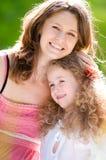 Madre joven que abraza a su hija Fotos de archivo