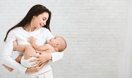 Madre joven que abraza a su niño recién nacido lindo imagen de archivo