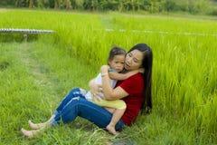 Madre joven que abraza y que calma una peque?a hija gritadora, a una madre asi?tica intentando confortar y calmar abajo a su ni?o imagen de archivo libre de regalías