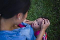 Madre joven que abraza y que calma una peque?a hija gritadora, a una madre asi?tica intentando confortar y calmar abajo a su ni?o foto de archivo libre de regalías